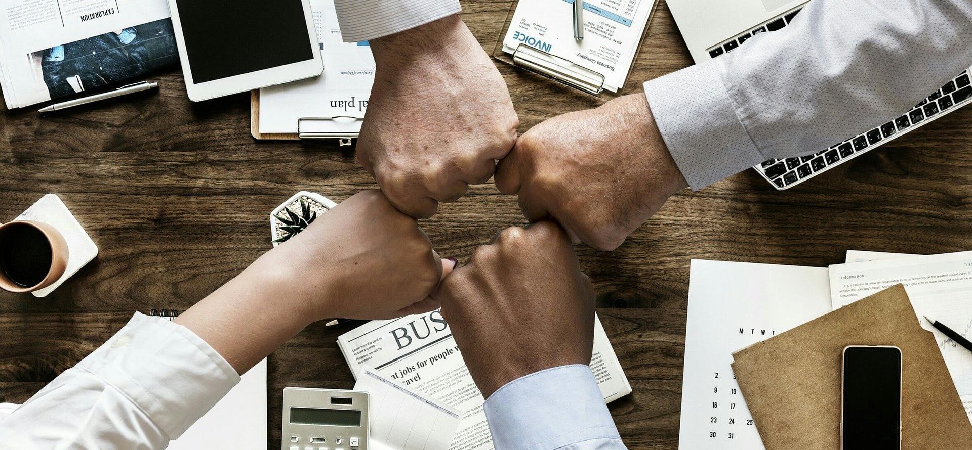 uniendo los puños en señal de equipo de trabajo por personal de ambos sexos